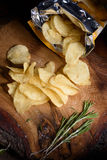 Top view on potato chips with fresh rosemary on wooden board. Open bag of salty snack. Royalty Free Stock Images