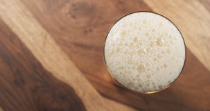 Top view poured lager beer from bottle into glass on wood table Stock Photography