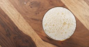 Top view poured lager beer from bottle into glass on wood table Royalty Free Stock Image