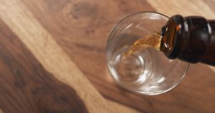 Top view pouring lager beer from bottle into glass on wood table Stock Image