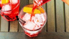 Top of view of pouring red spritz aperitif aperol cocktail with orange slices and ice cubes stock footage