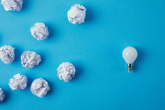 Top view of power saving light bulb with crumpled papers. On blue tabletop stock images