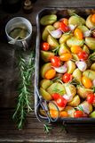Top view of preparation grilled potato with garlic and tomatoes Stock Image