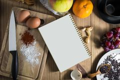 Top view of prepare cooking. Top view of prepare cooking : white notebook and eggs, knife, flavoring on chopping board. and tea cup, fruit, spoon, fork on Royalty Free Stock Image