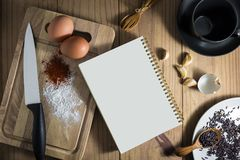 Top view of prepare cooking. Top view of prepare cooking : white notebook and eggs, knife, flavoring on chopping board. and tea cup, fruit, spoon, fork on Stock Images