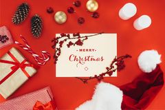 Merry christmas greeting card. Top view of presents, christmas decorations and Merry christmas greeting card, isolated on red royalty free stock photo
