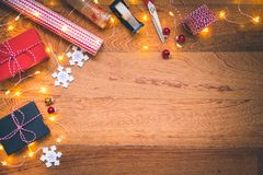 Top view of presents, wrapping equipment, Christmas snowflake decorations, Christmas balls and lights on wooden background royalty free stock image