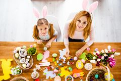 Top view of pretty beautiful mummy teaching her cute joyful small daughter paint decorate easter eggs together wearing rabbit cos. Tume having easter objects stock image