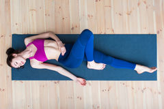 Top view of pretty skinny young Caucasian woman wearing sportswear lying on mat relaxing after workout in gym Royalty Free Stock Images