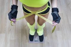 Top view of pretty slim woman with measure around her body standing on scales. Fitness woman dressed in sport outfit measuring her royalty free stock photos