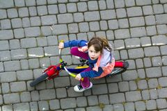 Top view of pretty young girl with long light brown hair riding a bicycle on cool spring day looking upward. Outdoors activities.h. Ealthy lifestyle and happy royalty free stock photos