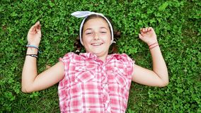Top view pretty young girl lying in the park on the grass stock video footage