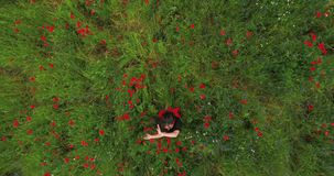 Top view. Pretty young woman wearing headphones listening to music and dancing in a poppy field smiling happily stock footage