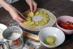 Top view on the process of making vegetable pizza, female hands spread out the zucchini on the dough.  Stock Photo