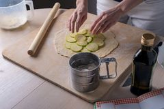 Top view on the process of making vegetable pizza, female hands spread out the zucchini on the dough.  Royalty Free Stock Images