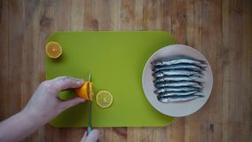 Addition to fish small pieces of lemon. Top view of a process of male hands cutting a lemon into round flat slices of a knife on a green cutting board, next to stock footage