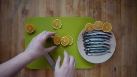 Addition to fish small pieces of lemon. Top view of a process of male hands cutting a lemon into round flat slices of a knife on a green cutting board, then stock footage
