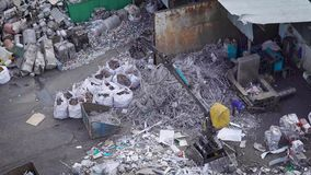 The process of processing materials, the machine where a person sits, raises garbage and shifts it into a metal basket stock video footage