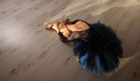 Top view of professional ballerina in blue tutu and pointe shoes sit and stretching on floor. Copyspace. Beautiful Young Woman Ballerina Stretching Warming Up Stock Photo