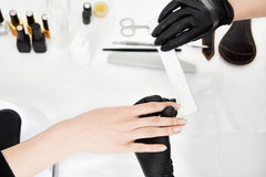 Top view. Professional nail tech in black goves shortening nails. Top view of professional nail tech in black goves shortening nails with square nail file Stock Image