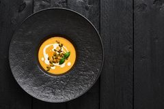 Top view of pumpkin and carrot soup with pumpkin seeds and cream royalty free stock images