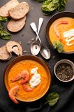 Pumpkin soup with shrimps, sour, pumpkin seeds in dark bowls and bread, greenery, silver spoons on black background royalty free stock image