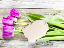 Top view of purple tulips and blank paper for text on wooden bac. Kground. Advertisement, valentines day, greeting and holidays concept Stock Photography