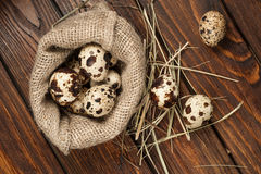 Top view on quail eggs in burlap sack over old wooden background Stock Photo