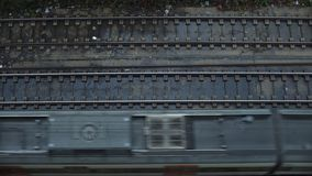 Top view on passing trains. Top view on railroad tracks and fast mid distance train is passing through on bottom side of image. Commute and travel concept stock footage