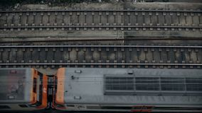 Top view slow motion on trains. Top view on railroad tracks with passenger short distance electric train slowly passing by in bottom lane from left to right stock video