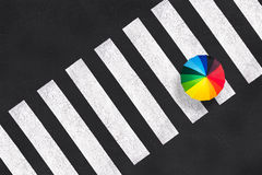 Top view of a rainbow umbrella on a pedestrian crosswalk. Aerial view of a rainbow umbrella on a pedestrian crosswalk stock image