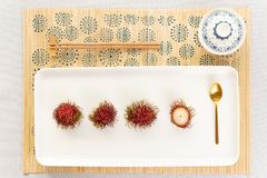 Rambutan desert top view with chinaware, golden spoon and chopsticks. Elegant rambutan asian desert top view with traditional chinaware bowl for tea, golden royalty free stock photos