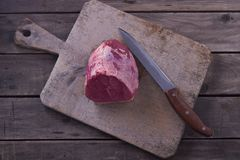 Top view raw beef meat on cutting board and knife on wooden background. Copyspace for your text. Top view raw beef meat on cutting board and knife on wooden Royalty Free Stock Image
