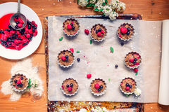 Top view Raw dough with berries for cupcakes decomposed into forms on a baking papper on baking tray decorated ewith flowers. Sele. Ctive focus. Vintage concept Stock Images