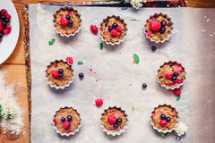 Top view Raw dough with berries for cupcakes decomposed into forms on a baking papper on baking tray decorated ewith flowers. Sele. Ctive focus. Vintage concept Royalty Free Stock Images