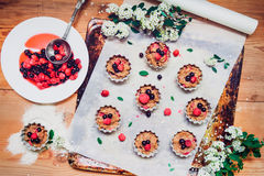 Top view Raw dough with berries for cupcakes decomposed into forms on a baking papper on baking tray decorated ewith flowers. Sele. Ctive focus. Vintage concept Stock Photography