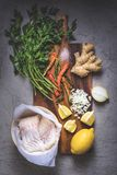 Top view of raw fish in bowl, parsley, peppers, salt, onion, lemon and ginger. On wooden cutting board Royalty Free Stock Images