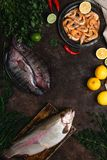 Top view of raw fish, chili peppers, shrimp, herbs with lemons and tablecloth Stock Images