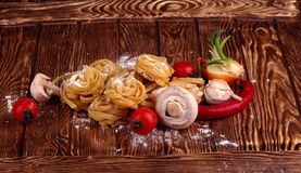 Top view on Raw homemade pasta with tomatoes,  and flour over old wooden table. Top view on Raw homemade pasta with tomatoes, mushrooms, onions and flour over royalty free stock images