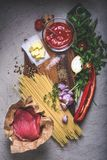 Raw meat, uncooked spaghetti, butter, tomato sauce and vegetables on cutting board Stock Images