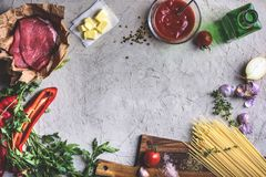 Top view of raw meat, uncooked spaghetti, butter, tomato sauce and vegetables Royalty Free Stock Image