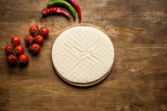 Raw pizza dough and vegetables. Top view of raw pizza dough, cherry tomatoes and chili peppers on wooden table Stock Images