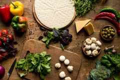 Raw pizza dough and vegetables. Top view of raw pizza dough and fresh vegetables on wooden cutting board Stock Photos
