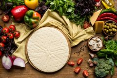 Raw pizza dough and vegetables. Top view of raw pizza dough and fresh vegetables on wooden table Royalty Free Stock Photo