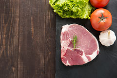 Top view raw pork on blackboard and vegetables on wooden backgro. Und Stock Photo