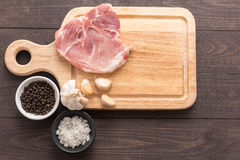 Top view raw pork chop steak and garlic, pepper on wooden backgr. Ound Royalty Free Stock Photography