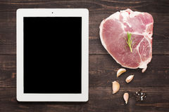 Top view raw pork chop steak and garlic, pepper on wooden backgr Stock Images