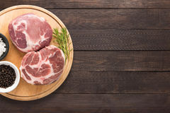 Top view raw pork chop steak and garlic, pepper on wooden backgr. Ound. Copy space for text Stock Image