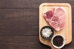 Top view raw pork chop steak and salt, pepper on wooden backgrou. Nd Royalty Free Stock Images
