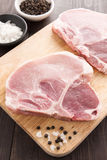 Top view raw pork chop steak and salt, pepper on wooden backgrou. Nd Royalty Free Stock Photos